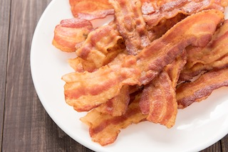 Closeup of fried bacon strips on white plate