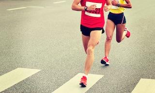 marathon runner legs running on city street