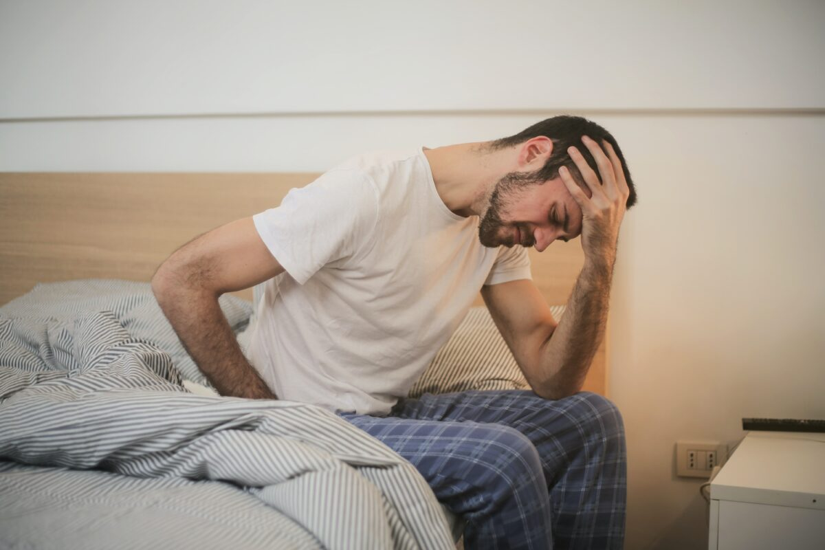 man waking up holding head and stomach because of inflammation