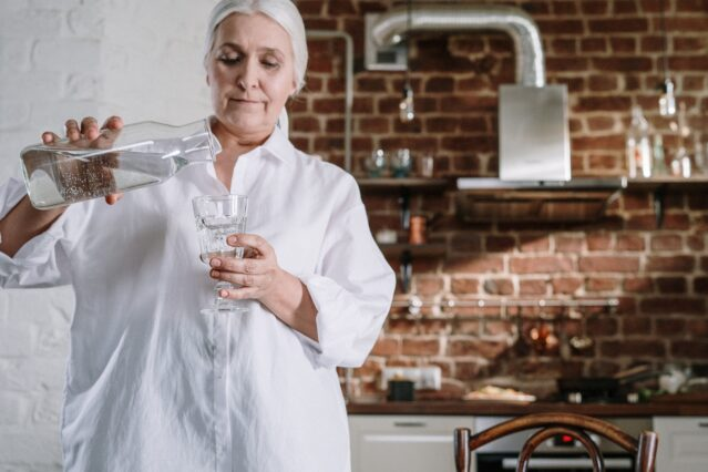 White-haired woman in white shirt standing in kitchen pouring water into a glass.