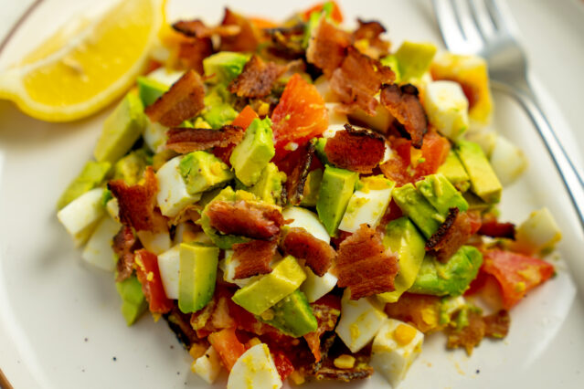 Chopped bacon, egg, avocado, and tomato salad on white plate with fork and lemon wedge.