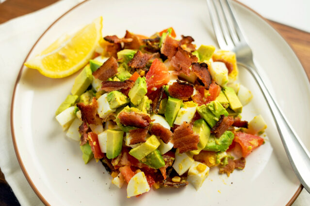 Bacon, egg, avocado, tomato salad on white plate with form and lemon wedge