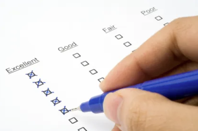 Hand holding a blue pen checking off boxes in columns labeled excellent, good, fair, poor