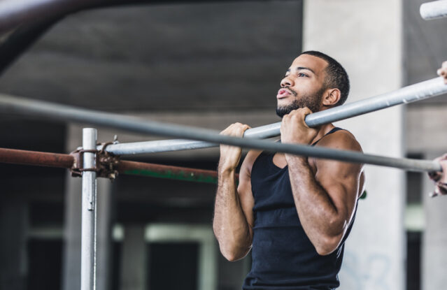 Male Athlete Doing Chin-ups in a Gym