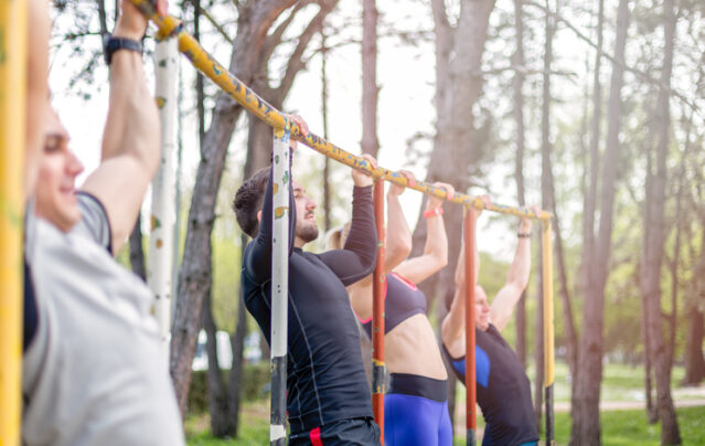 group of men and women performing negative pull-ups for pull up training at a park