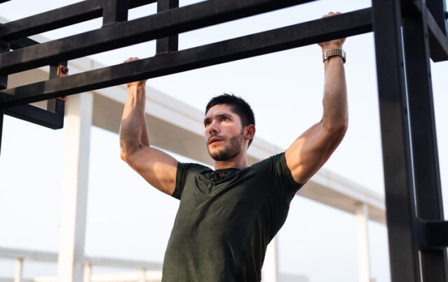 Man does pull-up on outdoor beam
