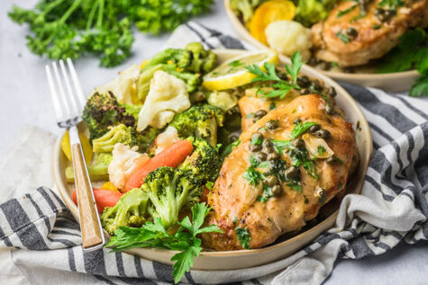 gluten free lemon caper chicken on a plate with a side of vegetables