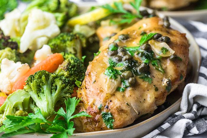 gluten free lemon butter caper chicken on a platter with mixed vegetables