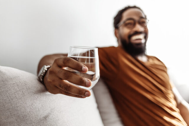 Cropped shot of a young man drinking a glass of water at home
