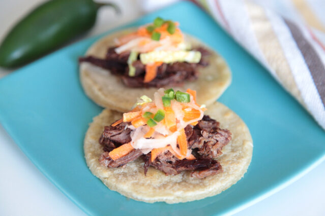 Street tacos on blue plate with shredded meat and vegetables, jalepeno pepper
