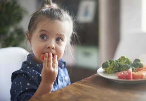 Young Child Eating Vegetables