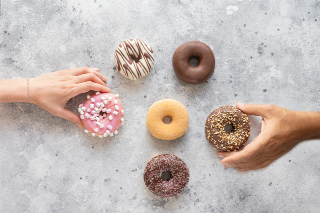 hands reaching for doughnuts