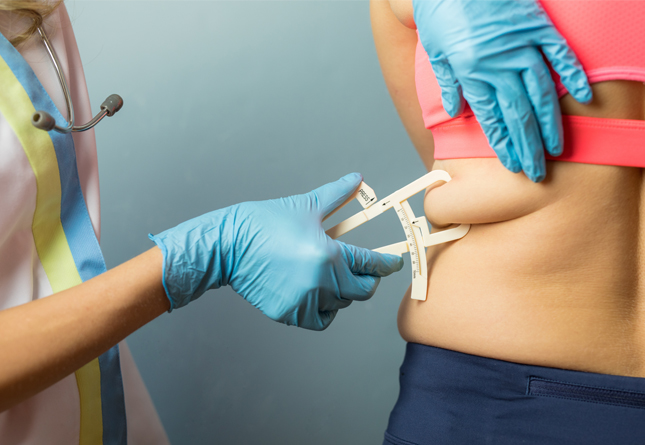 woman getting body fat measured with a caliper