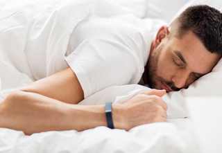 man sleeping with sleep tracker device