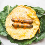 Collard green leaves layered underneath a keto egg wrap with a chicken sausage sliced in half. Primal Kitchen Buffalo Sauce tops the chicken sausage.