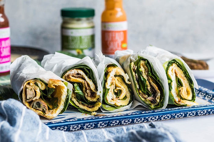 5 keto egg wraps wrapped in parchment paper on a white and blue serving platter. Primal Kitchen Buffalo Sauce and Primal Kitchen Pesto Mayo are in the background.