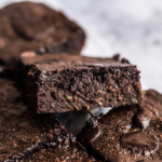 Keto Zucchini brownies are shown in squares, piled up.