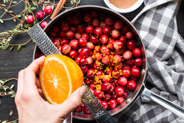 A hand zests an orange over a saucepan of fresh berries to make No sugar added cranberry sauce, with ingredients and a gingham towel in the background.