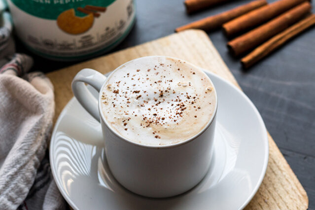 latte in a mug with cinnamon sprinkled on top