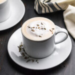 White mug of tea topped with frothed milk and lavender buds, sitting on white saucer.