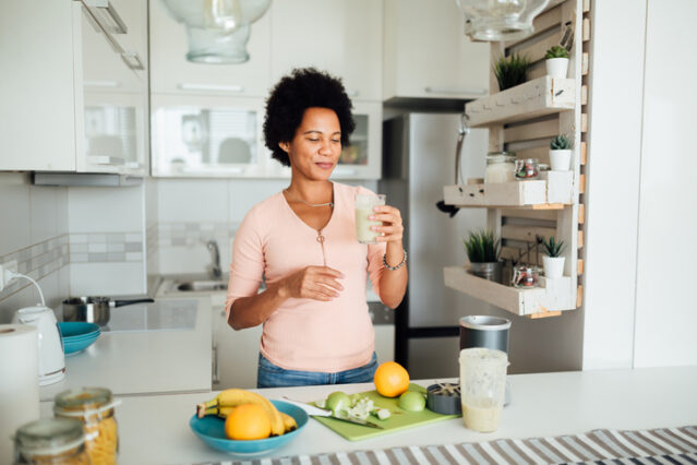 woman making and drinking a fresh green smoothie
