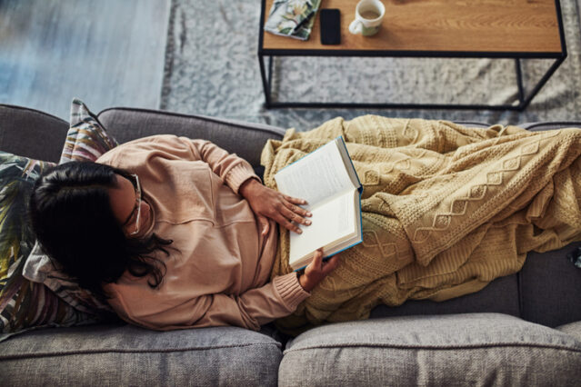 woman reading a book on the couch with a blanket