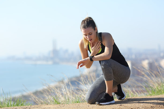 runner catching breath and checking heart rate to avoid chronic cardio