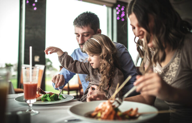 man and woman eating keto at a restaurant with their young daughter