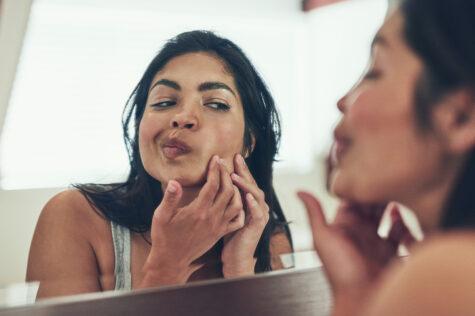 woman examining maskne in a mirror