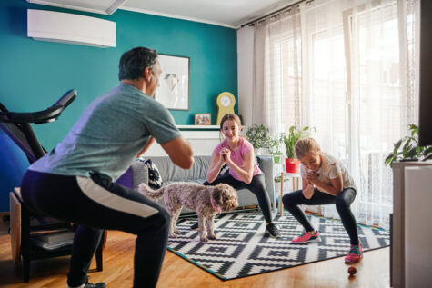 family practicing proper squat form in the living room