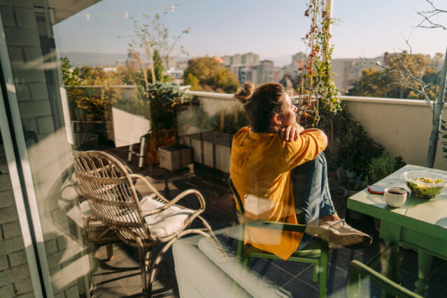 woman sitting outside on a patio as part of her morning routine