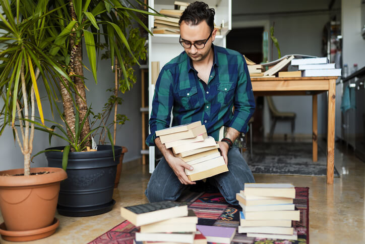 man decluttering books