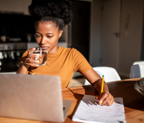 Woman drinking water while she focused on her online lecture