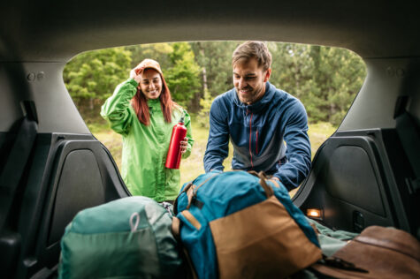 Photo of a smiling young couple, packing up camping equipment in the trunk of a car, ready for walking.