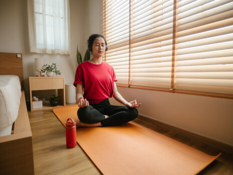 Relaxed young woman listening to music with headphones and fitness clothes in the modern house meditating.