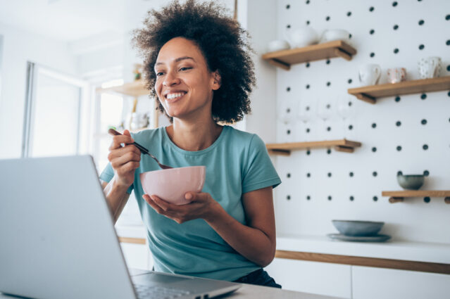 Beautiful young woman working from home. African-american woman working from home using laptop and having a breakfast. Businesswoman using laptop while she is in home isolation during coronavirus/COVID-19 quarantine.