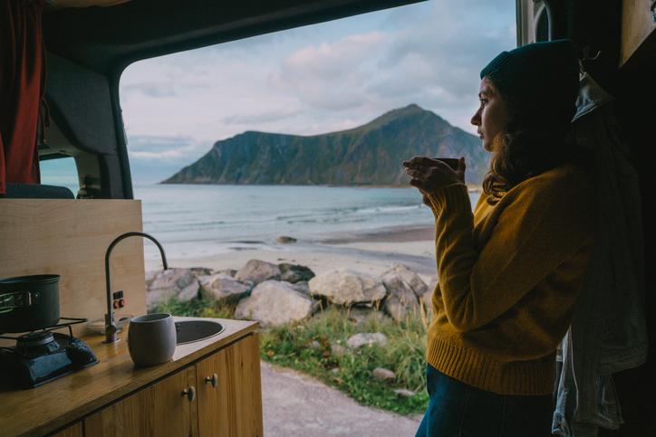 woman drinking blue lotus tea in a camper van near a lake