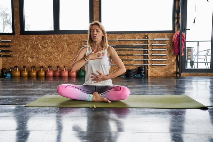 Middle life female yoga instructor exercising breathing on  <a href=
