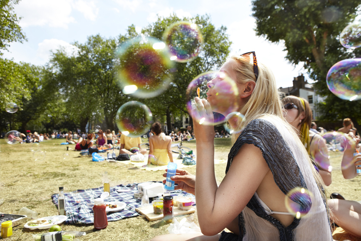 going dry sober curious woman blowing bubbles at a picnic with friends