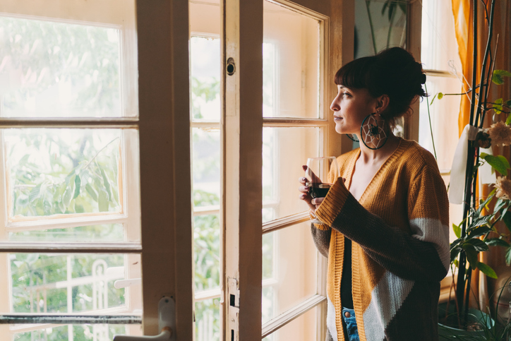 woman looking outside sipping a mug