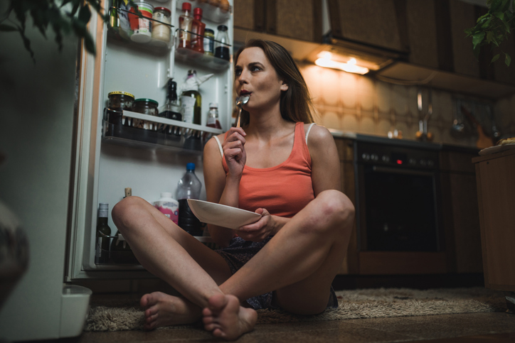Woman looking for midnight snack in the refrigerator