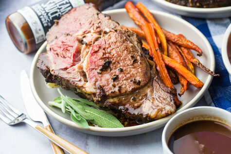 smoked prime rib on a plate from a smoking meat without a smoker recipe