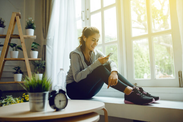 woman resting after an intense workout in home, talking on the phone, flare light