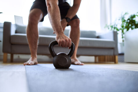 Closeup of man grabing kettlebell during home barefoot workout exercises