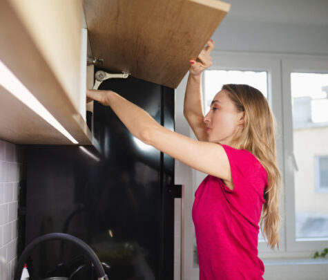 Blonde woman opening upper kitchen cabinet and reaching in