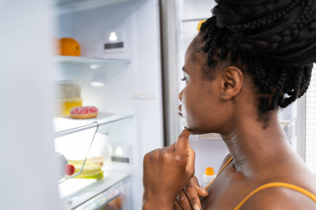 woman feeling hungry after exercise looking in refrigerator