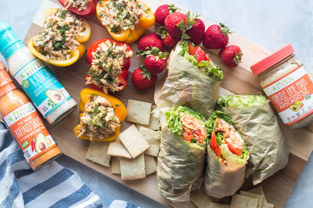 non-sandwich packed lunch options on a board including buffalo chicken stuffed peppers, chipotle chicken wraps, strawberries, and keto crackers arranged near Primal Kitchen products