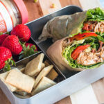 packed lunch with strawberries, keto crackers, and chipotle chicken lettuce wraps