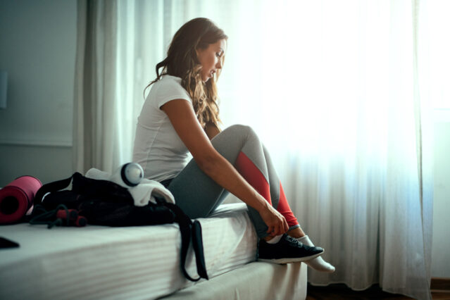 woman getting ready for fasted exercise next to her bed