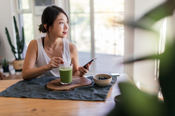 woman looking up collagen questions while drinking a smoothie